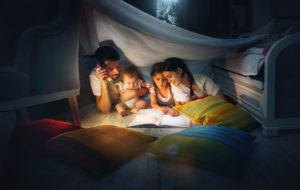 A small girl, baby girl, mother and dad reading book at home. Lifestyle, hapiness, family concept.